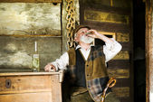 Farmer with glass of herbal spirit — Stock Photo