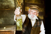 Farmer with bottle of herbal spirit — Stock Photo