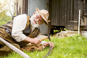 Farmer repairing his scythe — Stock Photo