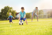 Father with sons playing football — Stock Photo