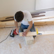 Handyman installing wooden floor — Stock Photo #47953613