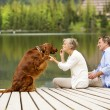 Couple with dog sitting on pier — Stock Photo #48399199