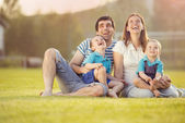 Family sitting on football pitch — Stock Photo