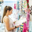 Woman choosing baby clothes — Stock Photo #49174525