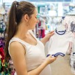 Woman choosing baby clothes — Stock Photo #49174593