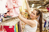 Woman choosing baby clothes — Stock Photo