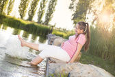 Pregnant woman relaxing by lake — Stock Photo