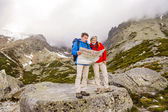 Hikers couple looking at hike map — Photo