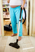 Woman is vacuuming floor — Stock Photo