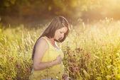 Schwangere frau sitzen auf wiese — Stockfoto