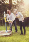 Couple pumping water from water pump — Stock Photo