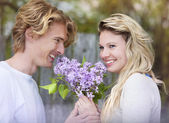 Couple with lilac flowers — Stock Photo
