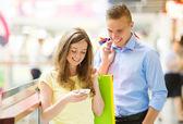 Casal com sacos em shopping center — Fotografia Stock