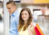 Couple with bags in shopping mall — Stock Photo