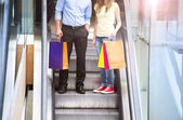 Couple go down the escalator — Stock Photo