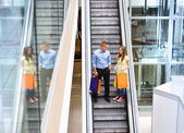 Couple go down the escalator — Stock Photo