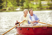 Senior couple paddling on boat — Stock Photo