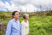 Senior couple at destroyed forest — Stock Photo