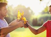 Men clinking beer bottles — Stock Photo