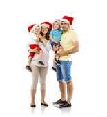 Glückliche familie in weihnachtsmützen — Stockfoto
