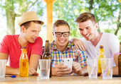 Three friends using smartphone — Stock Photo