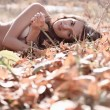 Woman lying on fallen leaves — Stock Photo #15350487