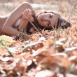 Stock Photo: Womlying on fallen leaves