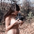 Woman in forest with camera — Stock Photo