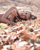 Woman lying on fallen leaves — Stock Photo
