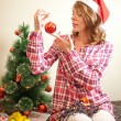 Beautiful woman hanging toy on Christmas tree — Stock Photo #15725917
