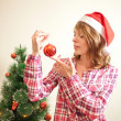 Beautiful woman hanging toy on Christmas tree — Stock Photo #15725983
