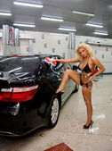 Beautiful woman in a black swimsuit washing a car — Stock Photo