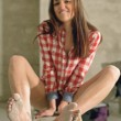 Attractive brunette in a plaid shirt — Stock Photo