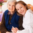 Young doctor holds the elderly woman hands — Stock Photo #15345065