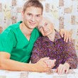 Elderly woman with the young smileing doctor — Stock Photo #15345191