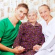 Elderly woman with the young doctors — Stock Photo