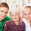 Elderly woman with the young doctors — Stock Photo #15345219