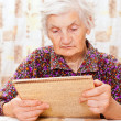 Foto de Stock  : Elderly happy womread something from book