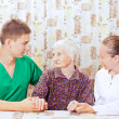 Elderly woman with the young doctor — Stock Photo #15345431