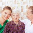 Elderly woman with the young doctors — Stock Photo #15345439