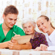 Elderly woman with the young doctors — Stock Photo #15345465