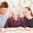 Elderly woman with the two young smileing grandchild — Stock Photo #15345477