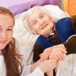 Young doctor holds the elderly woman hands — Stock Photo #15345575