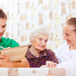 Elderly woman with the young doctors - Stock Photo