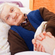 Elderly lonely woman rests in the bed - Stock Photo