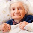Elderly lonely woman rests in the bed — 图库照片