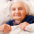 Elderly lonely woman rests in the bed - Foto Stock