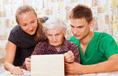 Elderly woman with the sweet young doctors — Stock Photo