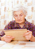 Elderly happy woman read something from the book — Stock Photo
