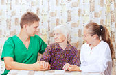Elderly woman with the young doctor — Stock Photo